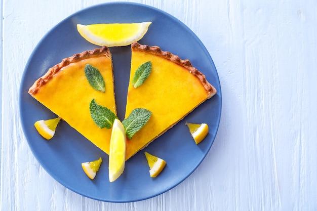 Assiette avec une délicieuse tarte au citron sur un mur en bois blanc