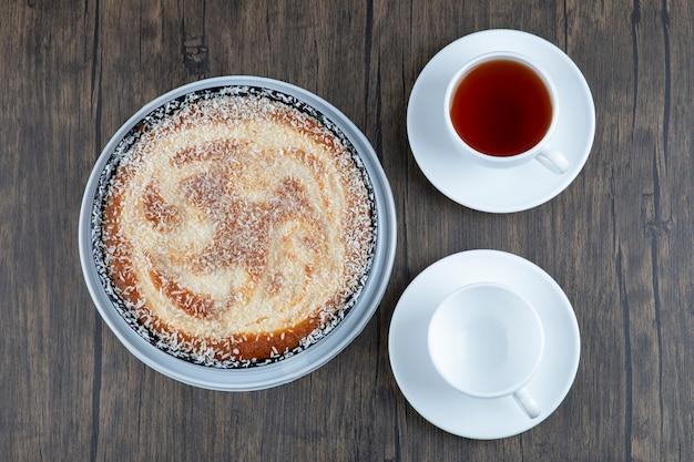Une assiette de délicieuse tarte avec une tasse de thé noir posée sur une table en bois.