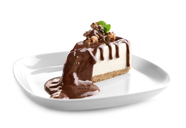 Assiette avec une délicieuse tranche de gâteau au fromage sur une surface blanche