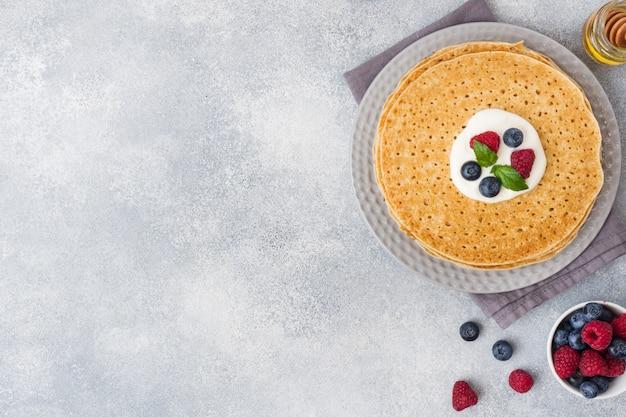 Assiette de délicieuses crêpes minces aux baies sur une table grise