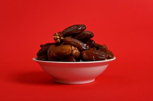 Une assiette avec de délicieuses dattes fraîches pour rompre le jeûne du ramadan, isolée sur fond rouge, espace de copie.