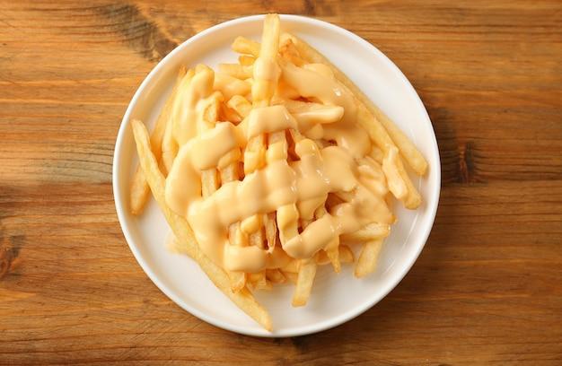 Assiette avec de délicieuses frites au fromage sur fond de bois
