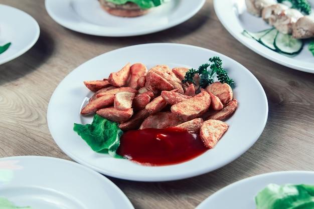 Assiette avec de délicieuses tranches de pommes de terre au four et sauce sur la table
