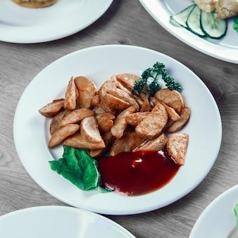 Assiette avec de délicieuses tranches de pommes de terre au four et sauce