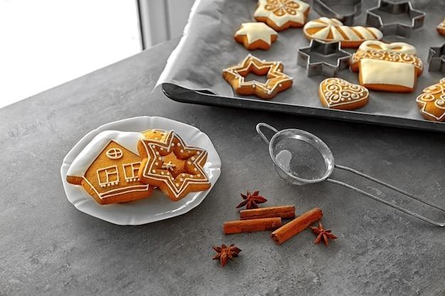 Assiette avec de délicieux biscuits de noël et épices sur table