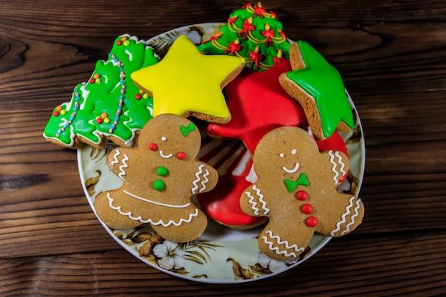 Assiette avec de délicieux biscuits de noël festifs en pain d'épice en forme d'arbre de noël, bonhomme en pain d'épice, étoile et bas de noël sur table en bois. vue de dessus