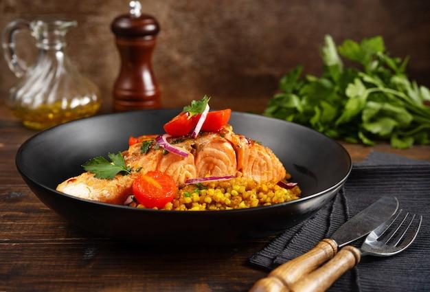 Une assiette avec un délicieux filet de saumon, des tomates cerises rôties et du sarrasin.