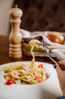 Assiette avec délicieux poulet alfredo sur table