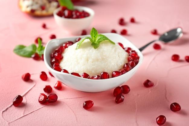 Assiette avec de délicieux riz au lait et graines de grenade sur la table des couleurs