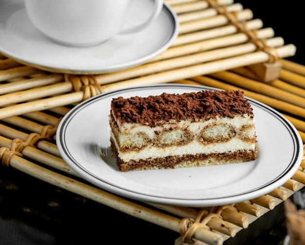 Assiette à dessert tiramisu italienne servie sur des planches de bambou