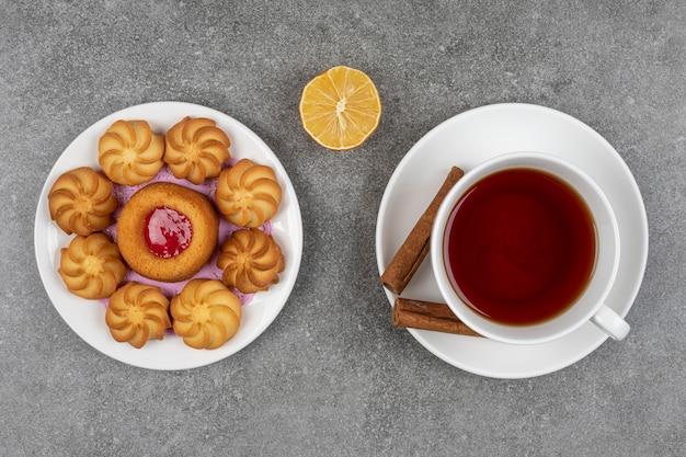Assiette de desserts et tasse de thé sur marbre.