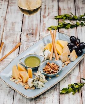 Assiette avec différents fromages et raisins, et verre de vin blanc