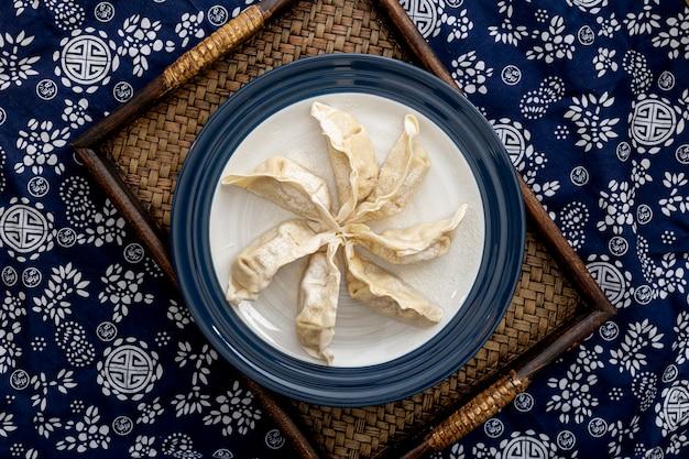 Assiette avec dim sum sur un socle en bois sur un fond floral bleu et blanc