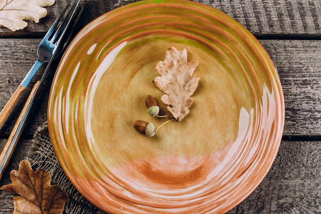 Assiette de dîner de thanksgiving avec fourchette, couteau et feuilles sur bois