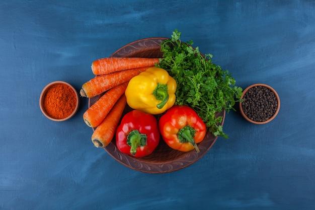 Assiette de divers légumes frais et mûrs sur une surface bleue.