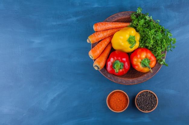 Assiette de divers légumes mûrs frais sur table bleue.