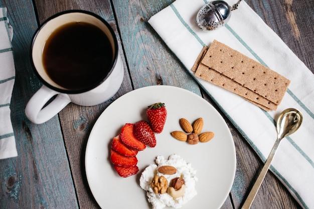 Assiette avec du fromage cottage, des fraises et des noix, une tasse de café et des serviettes sur une table en bois, des aliments sains, le petit déjeuner