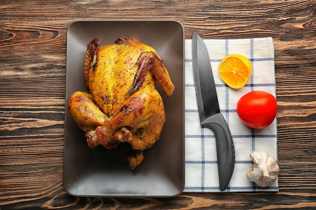 Assiette avec du poulet rôti canette de bière sur fond de bois