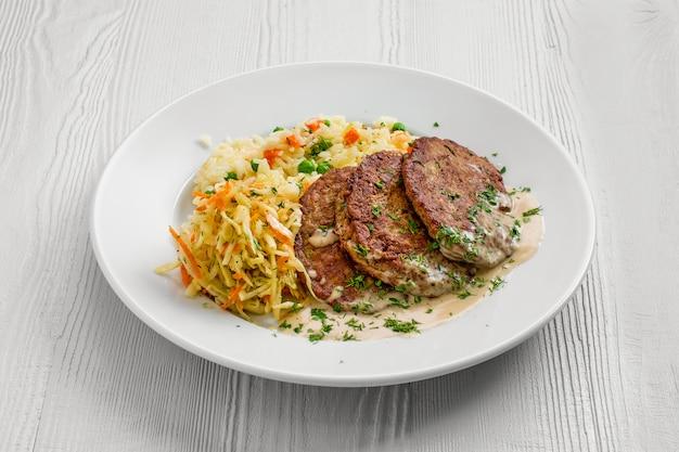 Assiette avec escalope de foie, riz aux petits pois et chou mariné
