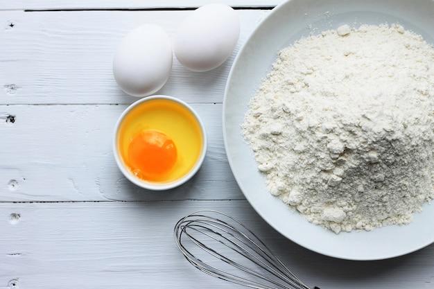 Une assiette avec de la farine, des œufs, un fouet sur un fond en bois blanc.