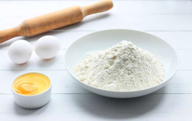 Une assiette avec de la farine, des œufs, un rouleau à pâtisserie sur un fond en bois blanc.