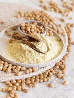 Assiette de farine de pois chiches crus et haricots sur table blanche close up