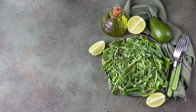 Assiette avec des feuilles de salade de mélange vert et microgreens, citron vert, avocat et huile d'olive
