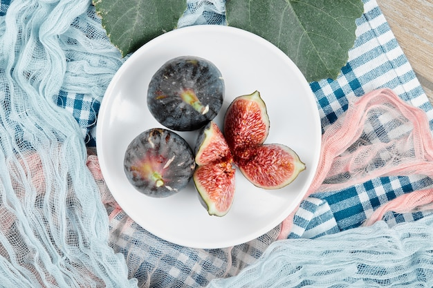 Une assiette de figues noires entières et tranchées, une feuille et des nappes bleues et roses sur une table en bois.