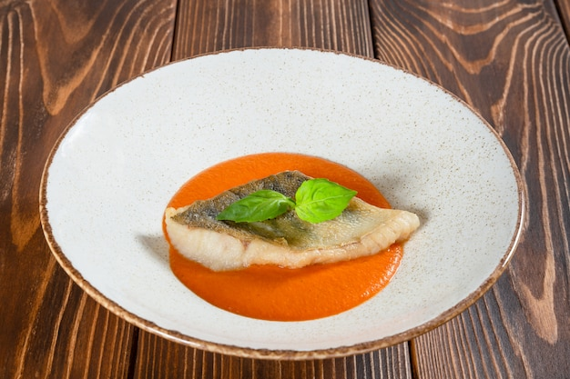 Assiette de filet de poisson avec sauce à la citrouille sur une table en bois