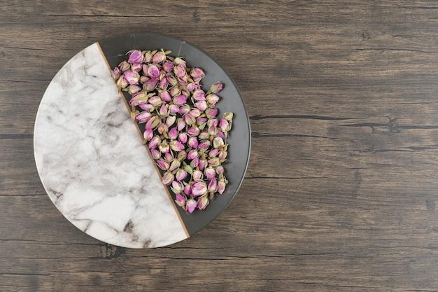 Une assiette avec des fleurs roses séchées sur un bois.