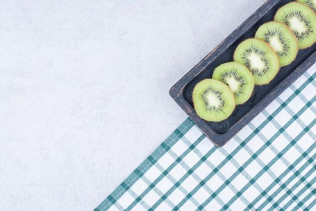 Une assiette foncée de kiwi frais tranché sur une nappe.