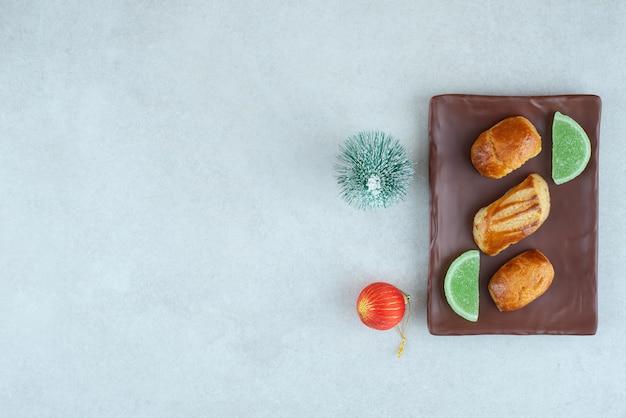 Une assiette foncée de pâtisseries sucrées avec de la marmelade et des jouets de noël.