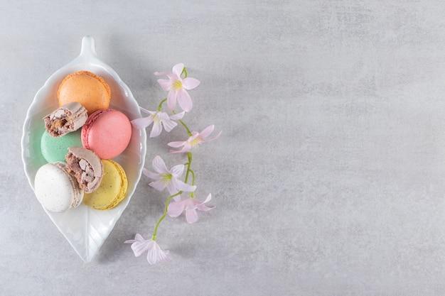 Assiette en forme de feuille de macarons sucrés colorés avec des fleurs sur la table en pierre.