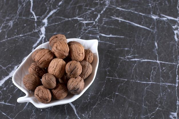 Assiette en forme de feuille pleine de noix saines posées sur un marbre.