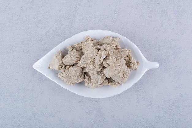 Assiette en forme de feuille de savoureux halva de tournesol sur pierre.
