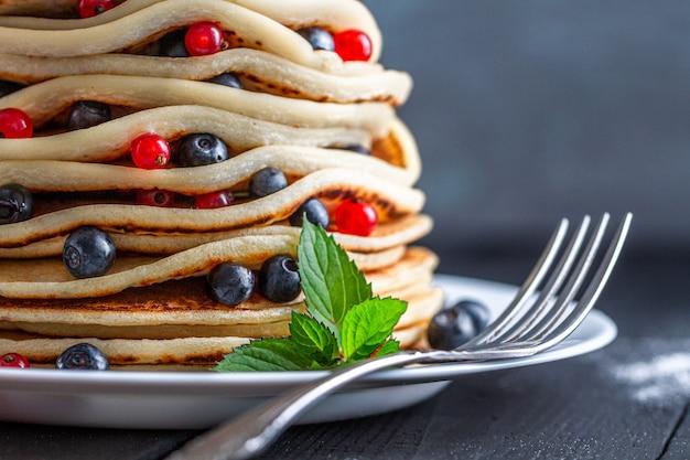 Assiette avec une fourchette et des crêpes américaines cuites au four maison avec des baies fraîches et de la menthe verte pour une délicieuse collation bouchent