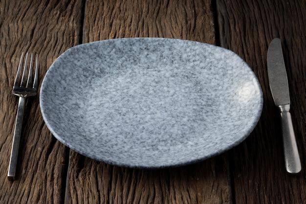 Assiette fourchette cuillère sur fond bois clair et sans profondeur de champ