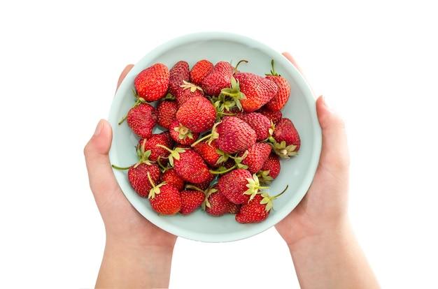 Assiette avec des fraises dans les mains