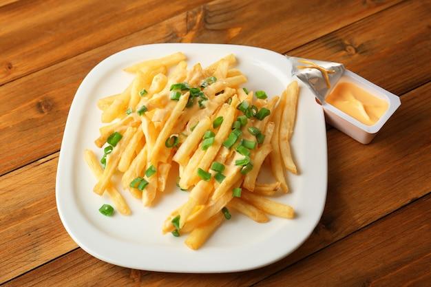 Assiette avec frites au fromage et oignon vert haché sur table en bois