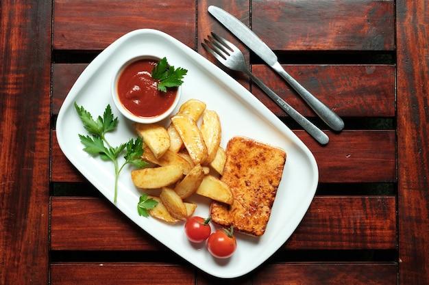 Une assiette de frites avec rattrapage, fond en bois