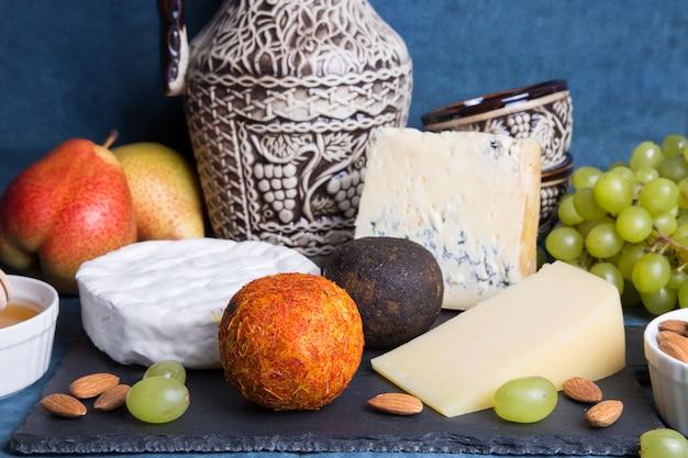Assiette de fromage. 5 espèces de fromages, fruits, noix, carafe à vin. gros plan, mise au point sélective.