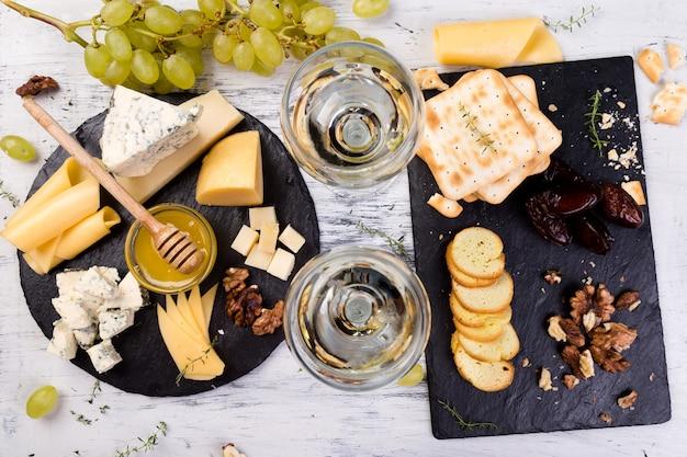 Assiette de fromage. assortiment de fromages aux noix, pain et miel sur une plaque ardoise.