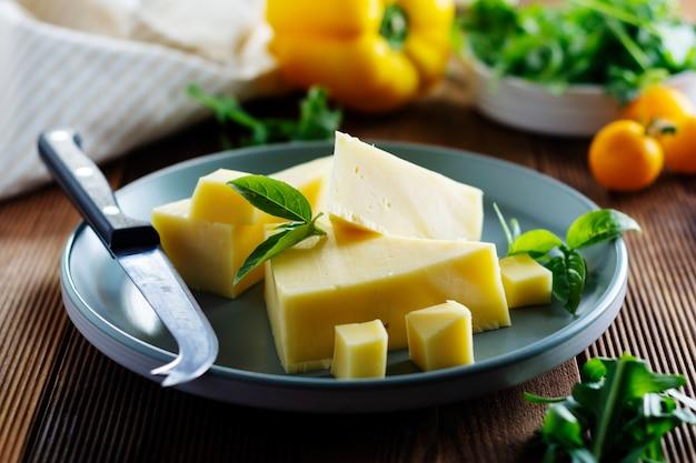 Assiette à fromage avec de délicieuses tranches de fromage et un couteau à fromage, table en bois.