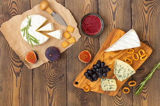 Assiette de fromage servie avec de la confiture, des figues, des craquelins et des herbes au bois