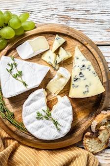 Assiette de fromages au camembert, brie et fromage bleu aux raisins. fond en bois blanc. vue de dessus.