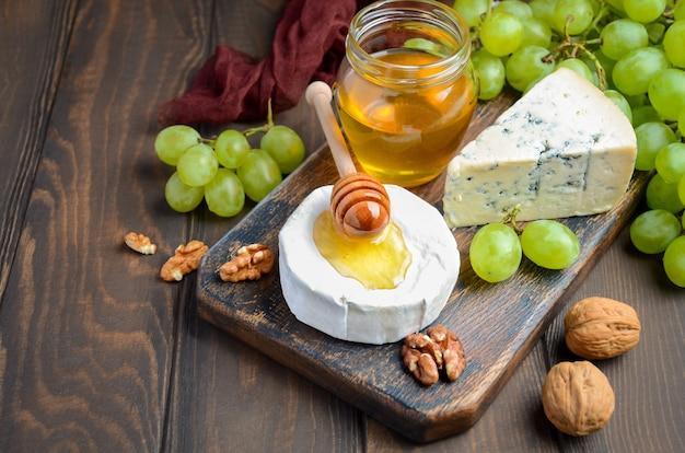 Assiette de fromages aux raisins, miel et noix sur fond sombre.