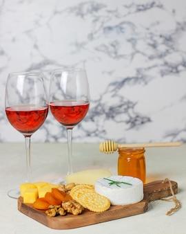 Assiette de fromages, camembert, romarin, craquelins, abricots secs et noix