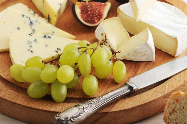Assiette de fromages avec divers types de fromages et de figues et des raisins sur une surface en bois blanche