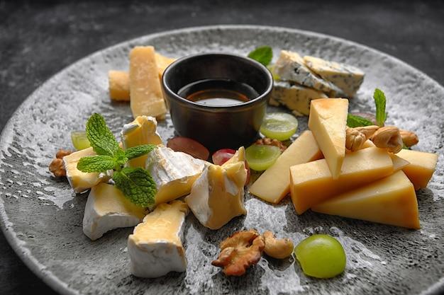 Assiette de fromages, fromages assortis à la menthe, fruits confits, miel et biscuits, sur une assiette