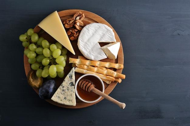 Assiette de fromages fromages, raisins, prunes, noix, bâtons de pain et miel
